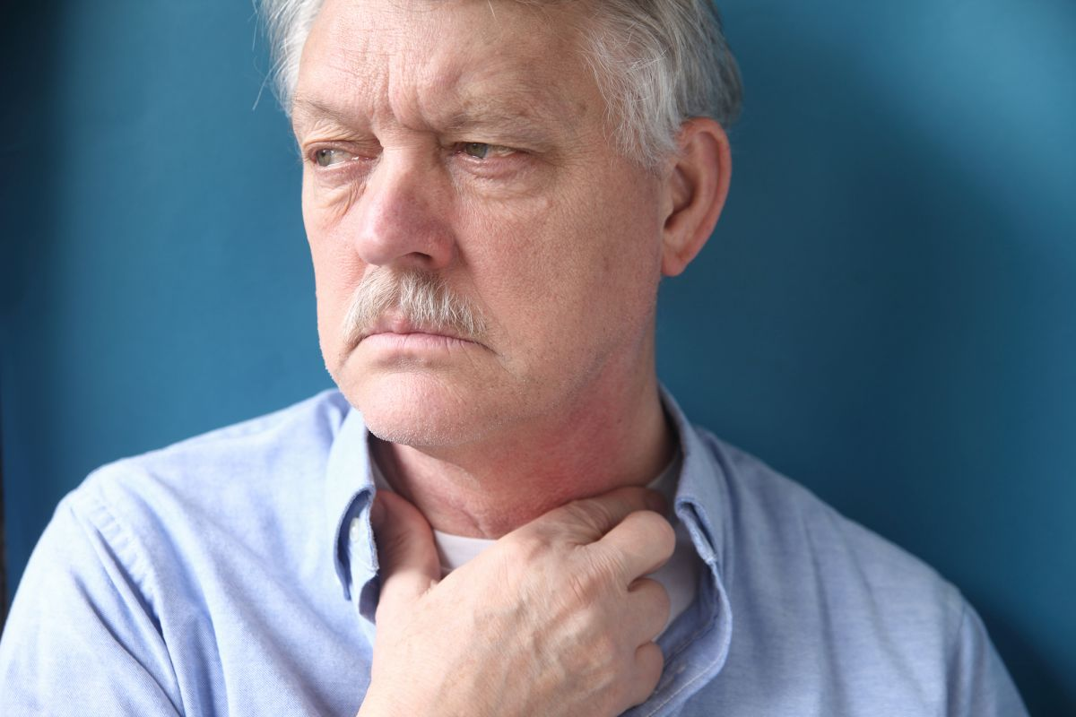 Senior man with throat or neck irritation